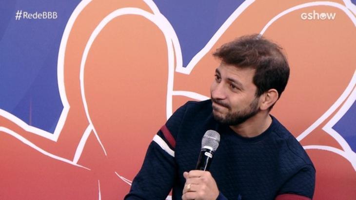 Caio Afiune sentado com microfone na mão