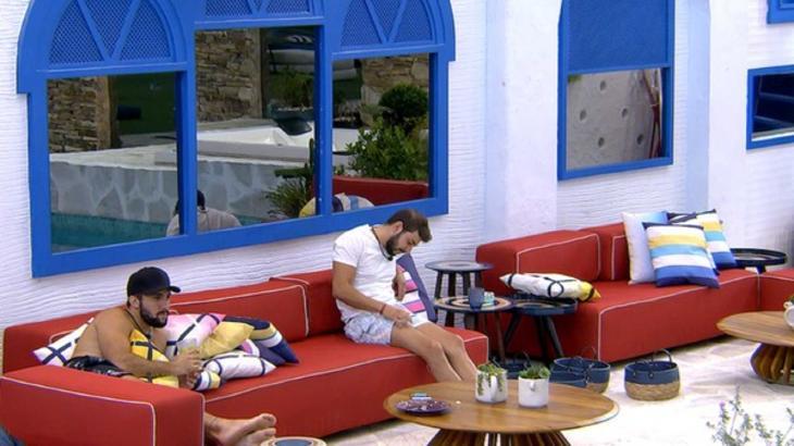 Caio e Arthur sentados durantes conversa na área externa do BBB21