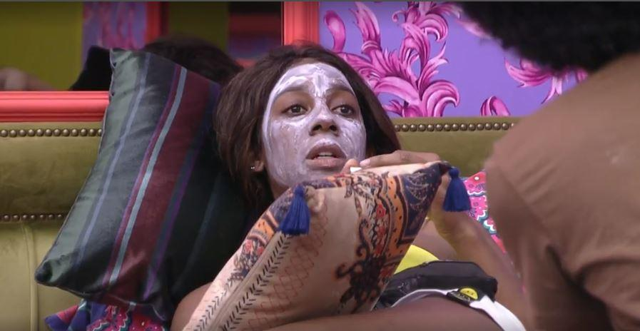 Camilla de Lucas está deitada na cama do quarto colorido com máscara facial