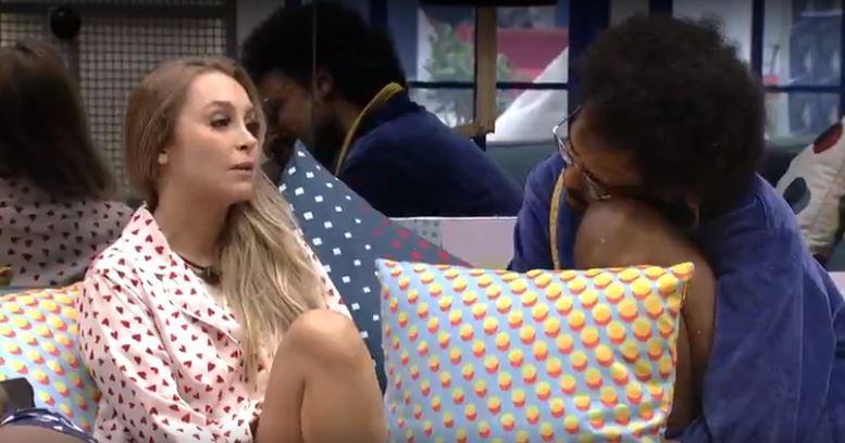Carla está na sala sentada ao lado de João Luiz