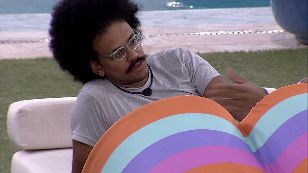 João Luiz gesticulando sentado na área externa do BBB21