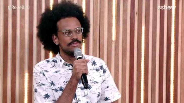 João Luiz sentado com microfone na mão