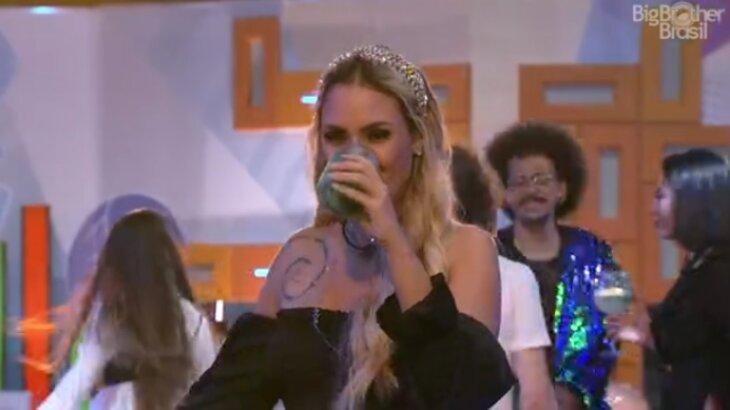 Sarah tomando bebida em festa