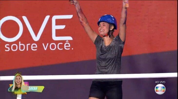 Sarah de braços levantados comemorando vitória