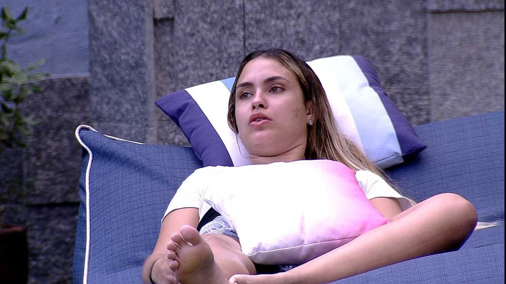 Sarah está deitada na espreguiçadeira na área externa