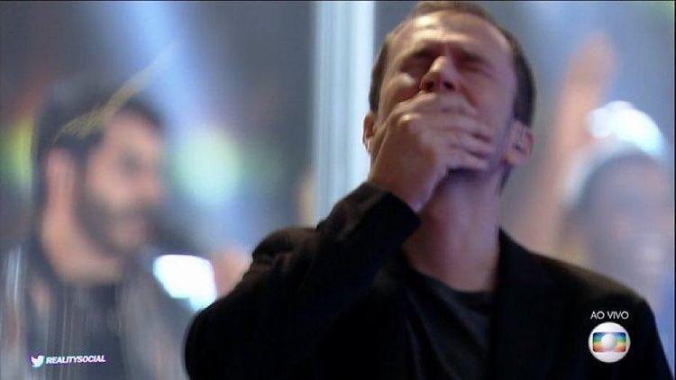 Tiago Leifert está chorando com os olhos fechados e a mão tampando a boca na final do BBB21