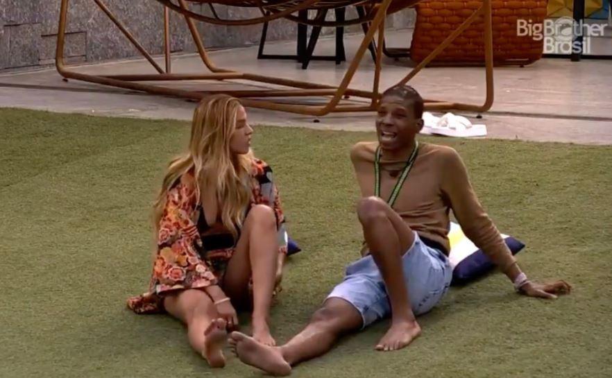 Sentados no gramado, na área externa, Lucas e Kerline tentam conversar no BBB21