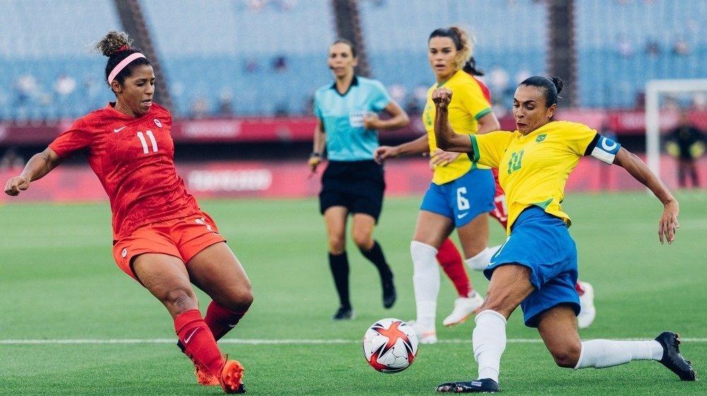 Marta chutando bola contra seleção canadense