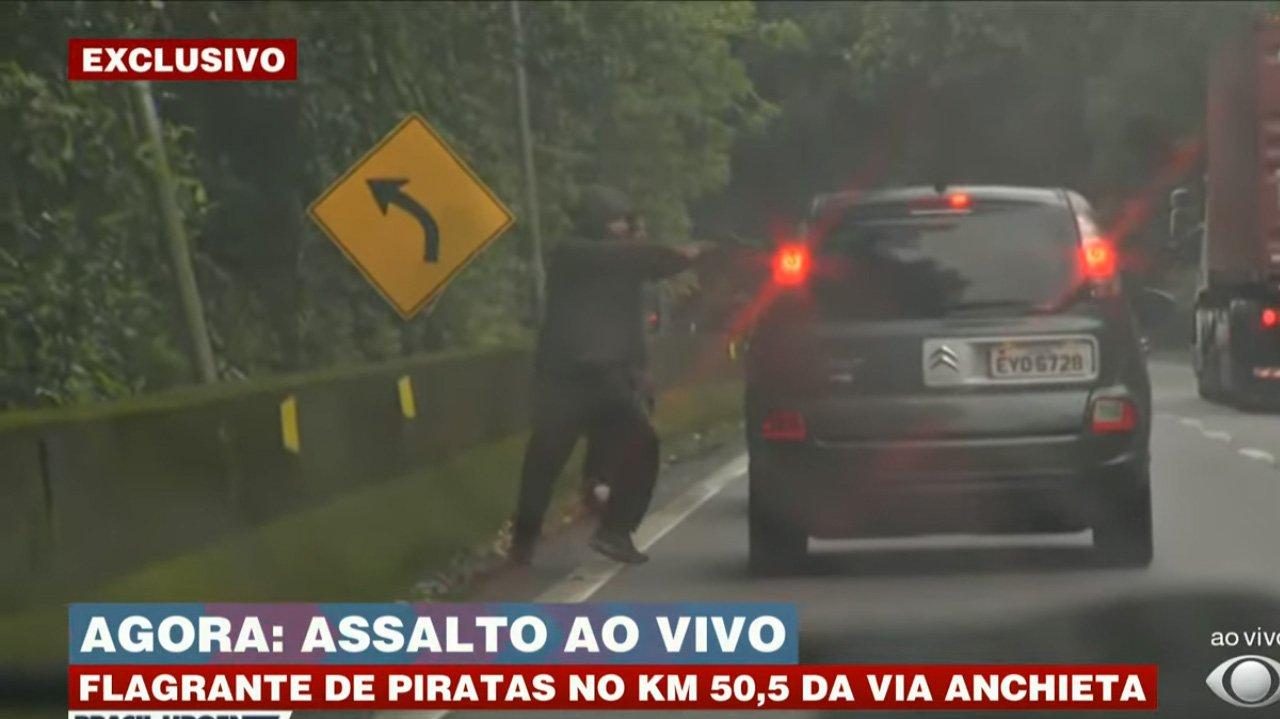 Assaltantes mirando arma para carro