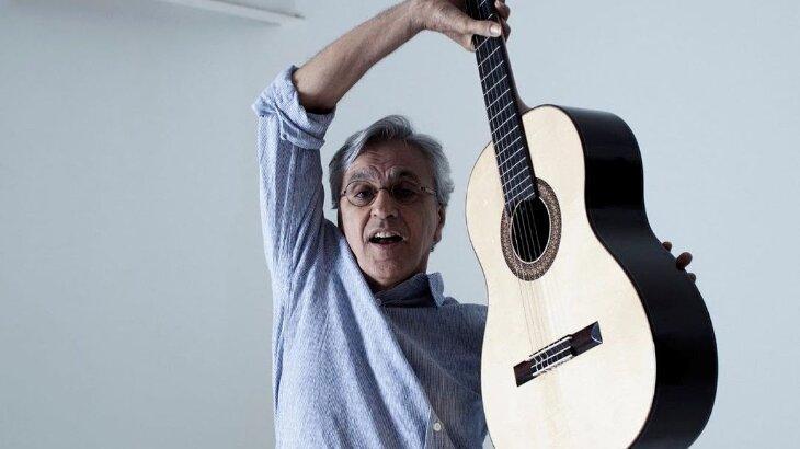 Caetano Veloso posado para foto segurando um violão no ar