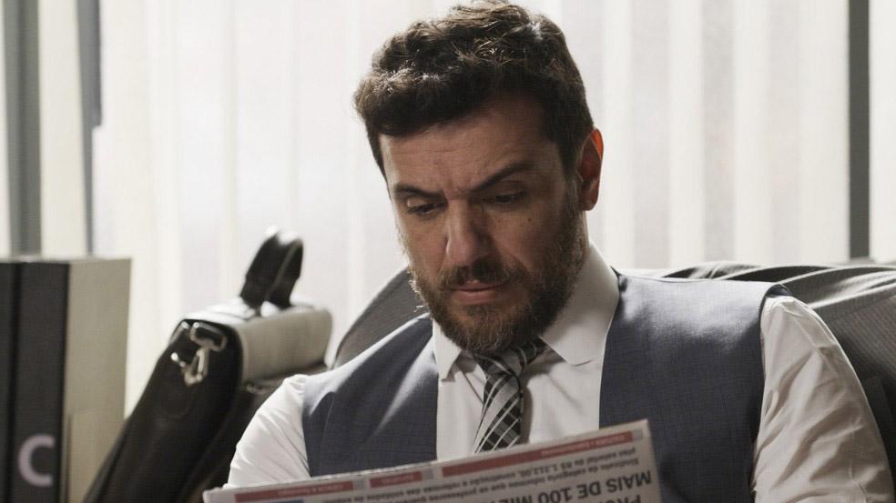Caio lendo jornal em A Força do Querer