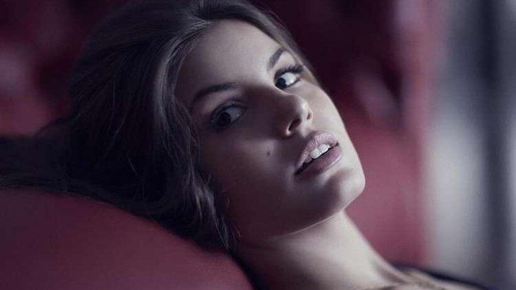 Camila Queiroz deitada olhando de rabo de olho