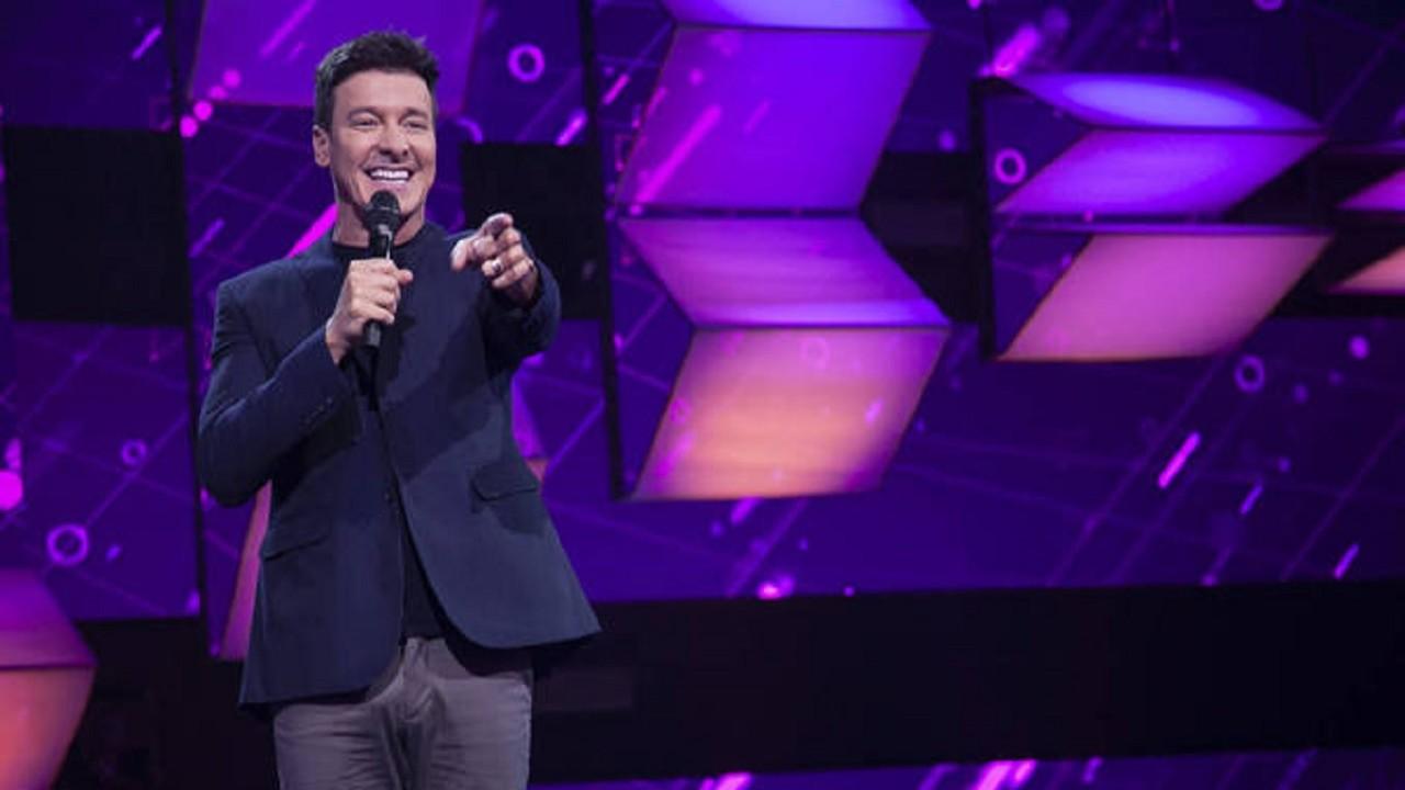 Rodrigo Faro segurando o microfone e apontando o dedo no palco do Canta Comigo Teen 2