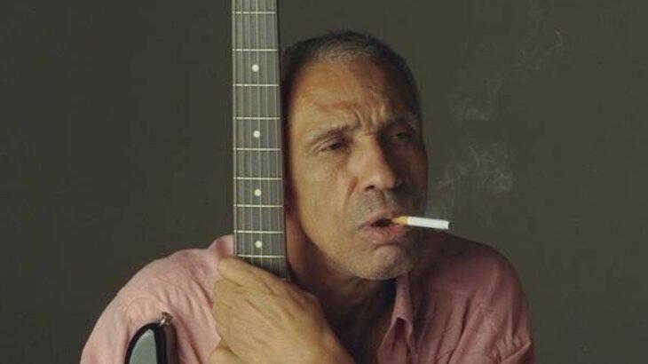 Cantor Cassiano agarrado em sua guitarra, fumando cigarro