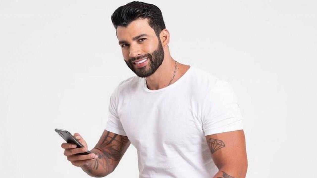 Cantor Gusttavo Lima sentado, sorrindo e segurando um celular