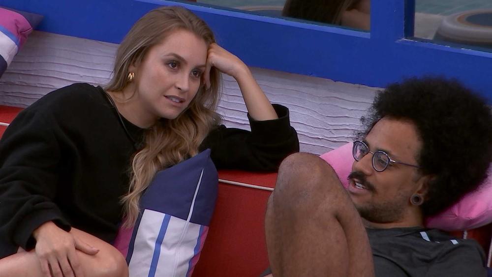 Carla Diaz com a mão na cabeça ao lado de João Luiz