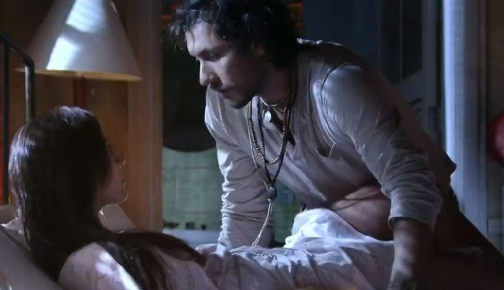 Carol deitada na cama enquanto que Lino se aproxima dela
