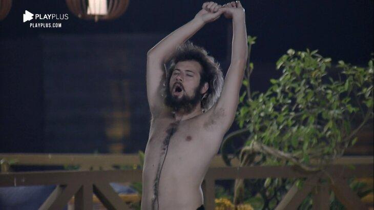 Lucas Cartolouco sem camisa, de braços levantados e olhos fechados