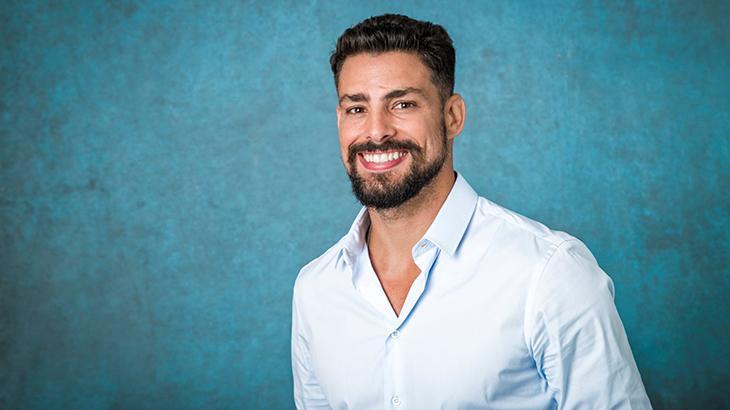 CAUã Reymond sorrindo com fundo azul