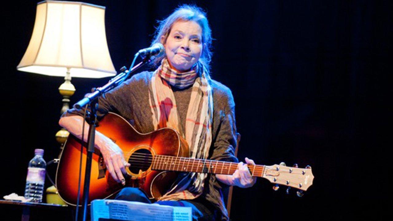 Nanci Griffith tocando violão e cantando em apresentação