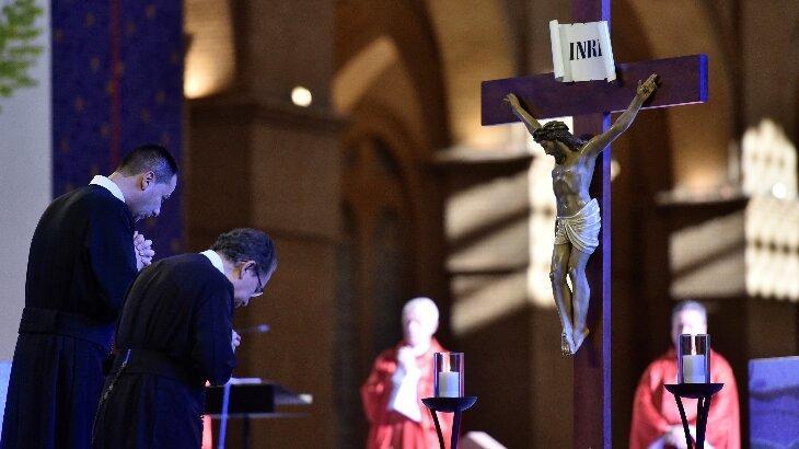 Momento da cerimônia em que dois sarcedotes fazem reverência a cruz