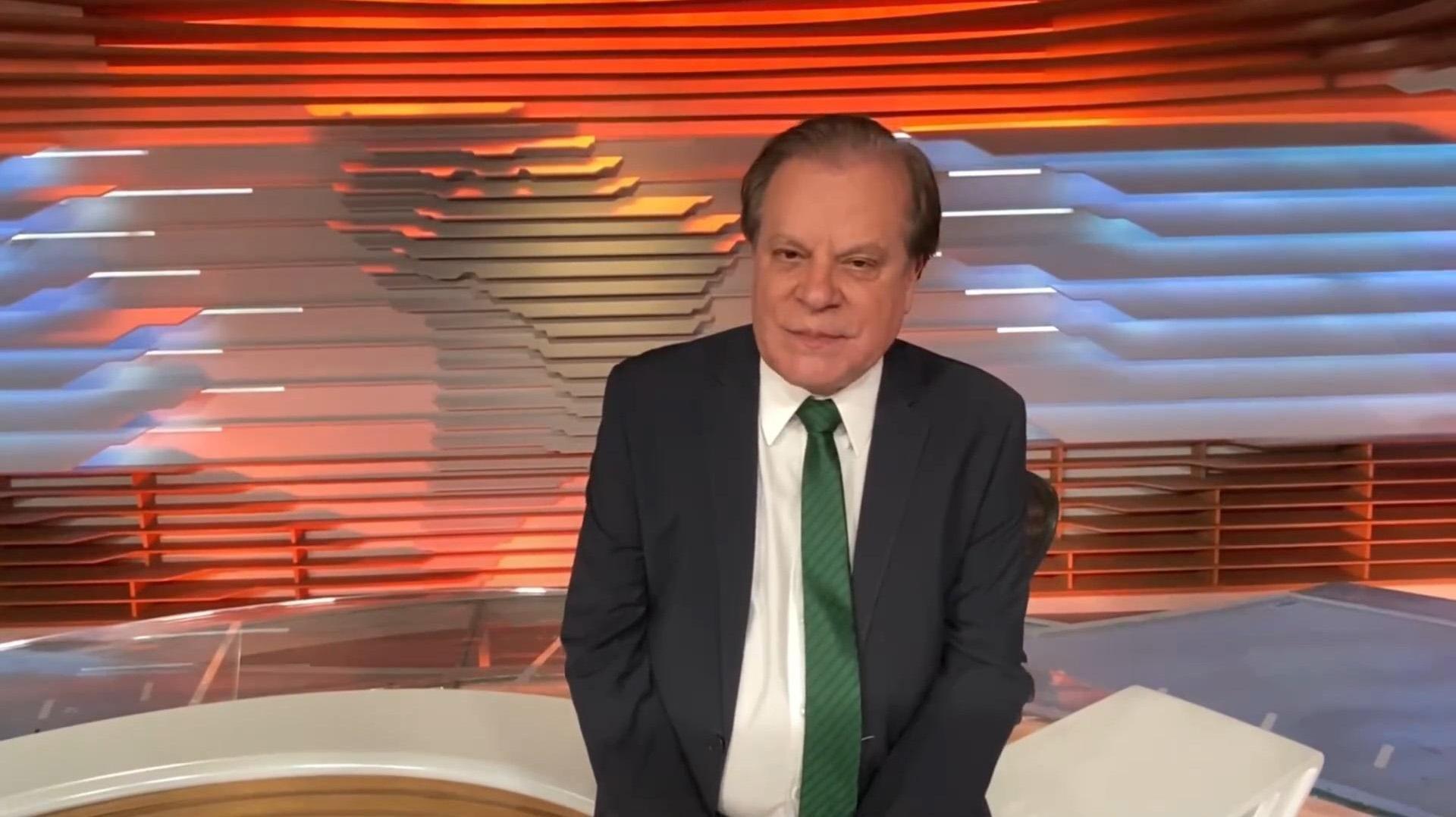 Chico Pinheiro encostado na bancada e de gravata verde