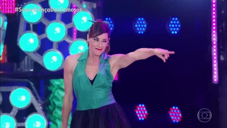 Cena da Super Dança dos Famosos com Christiane Torloni apontando o dedo para frente sorrindo