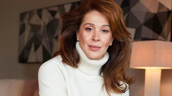 Cláudia Raia sentada perto de um abajur e com blusa de frio