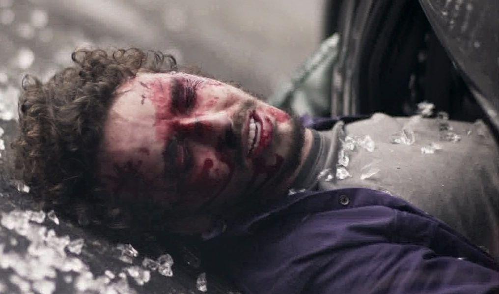 Cláudio está com a cabeça para fora do carro, por cima de alguns cacos de vidro, e o rosto todo ensanguentado