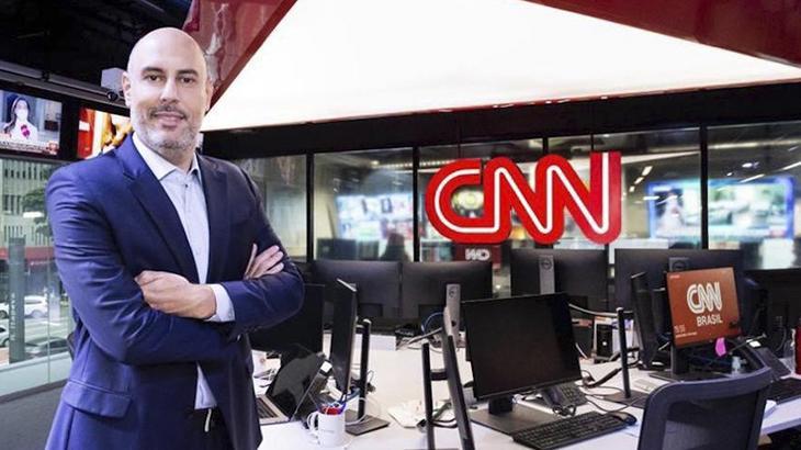 Douglas Tavolaro com os braços cruzados posando para fotos tendo ao fundo a redação da CNN Brasil