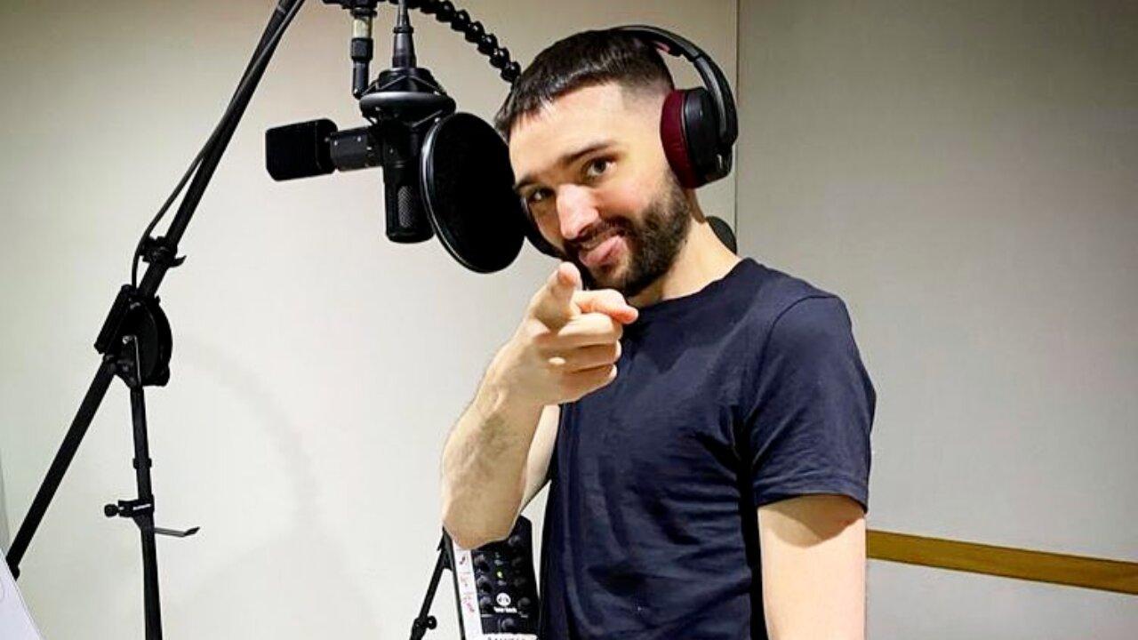 Tom Parker no estúdio de gravação, apontando dedo e língua pra fora, usando fone de ouvido