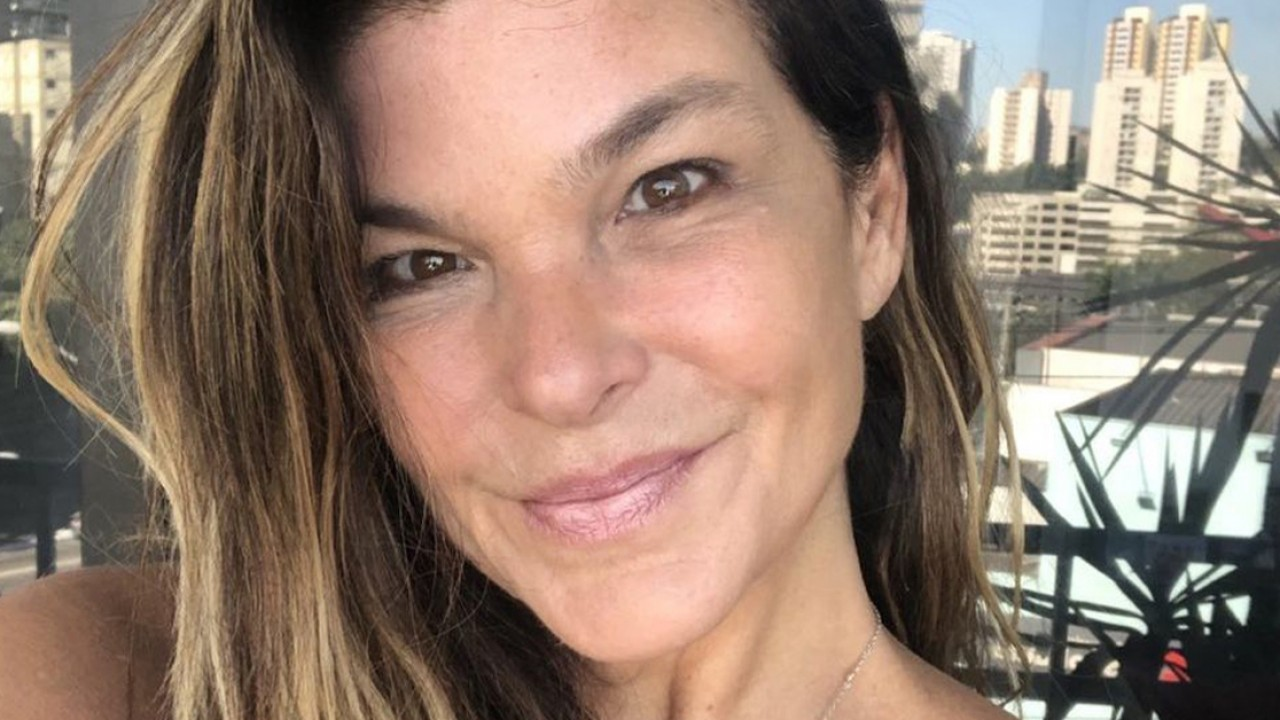 Cristiana Oliveira sorrindo com prédios ao fundo