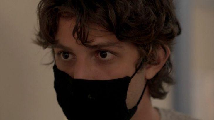 Cena de Amor de Mãe com Danilo olhando para frente, usando máscara de proteção