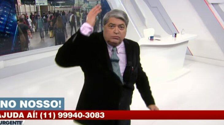 Datena com raiva durante programa, com a mão levantada