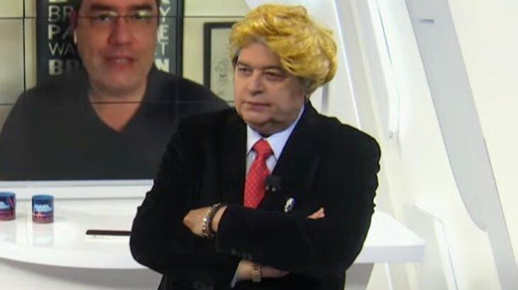 Datena de braços cruzados com uma peruca loira