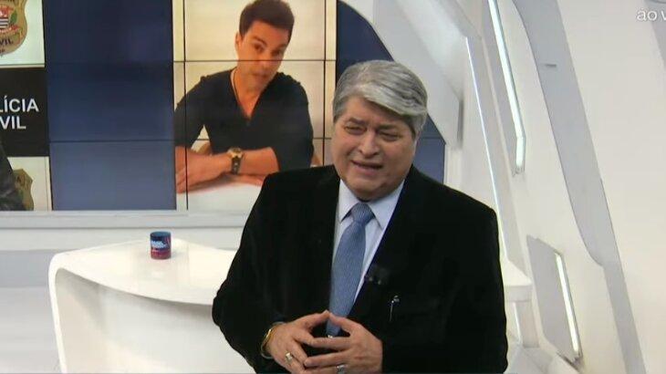 Com Zezé di Camargo no telão ao fundo, Datena faz cara de reprovação