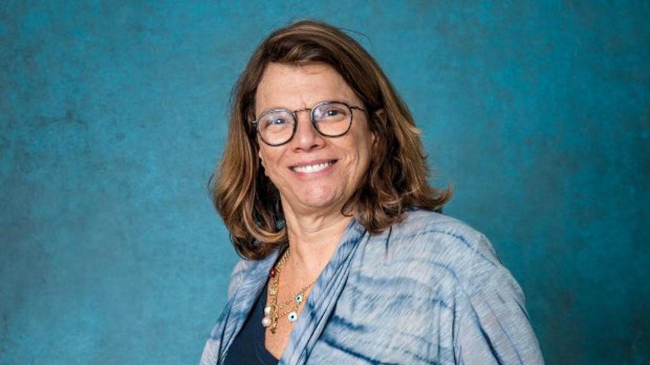 Denise Saraceni sorrindo em fundo azul