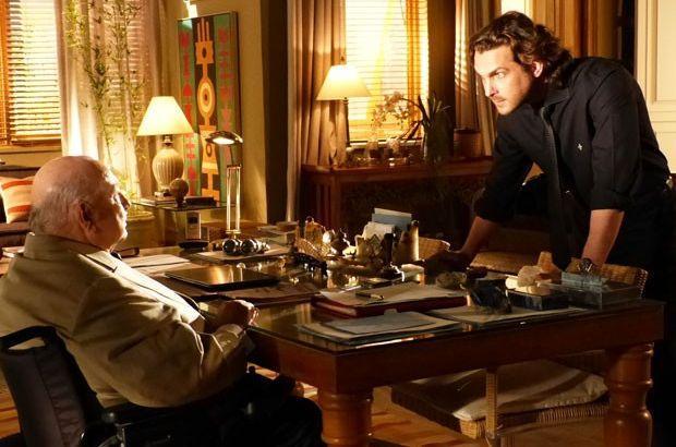 Alberto inclina sobre a mesa de Dionísio e o enfrenta