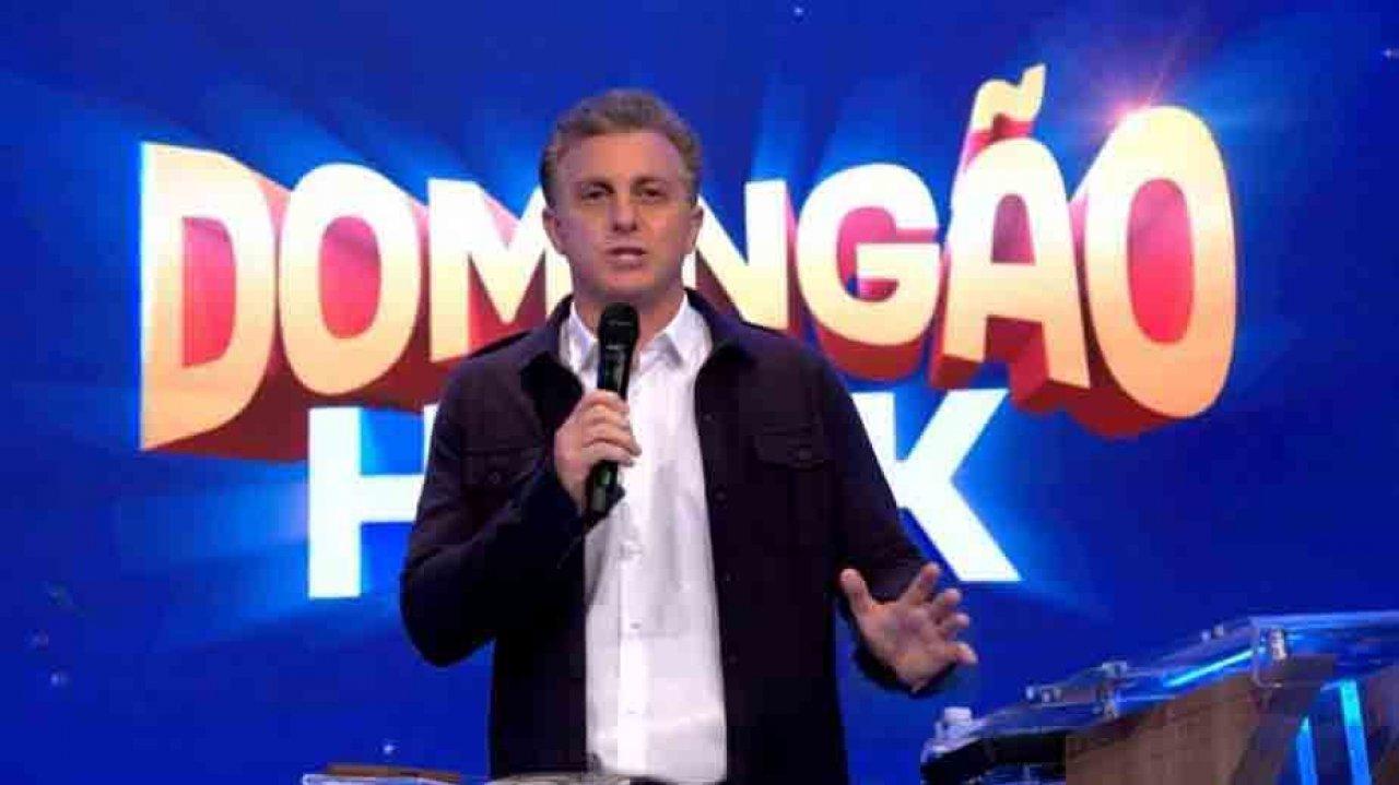 Luciano Huck com microfone na mão e gesticulando no Domingão