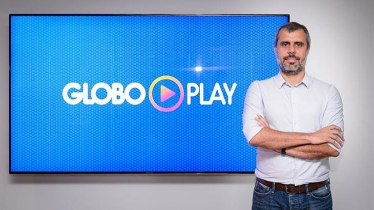 Érick Bretas de braços cruzados e de pé posa para foto com um telão ao fundo com o logo do Globoplay