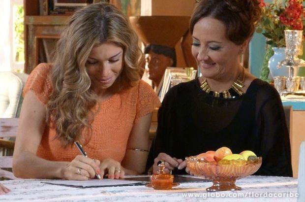Ester olha para a escritura enquanto assina e Guiomar a observa, sorrindo