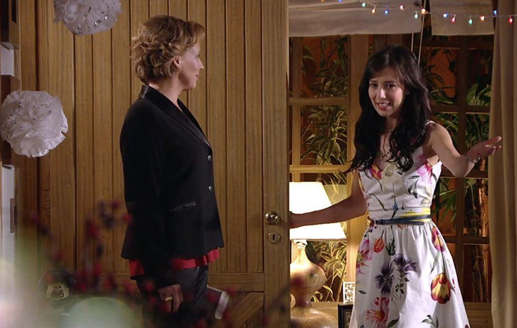 Eva em é na porta enquanto que Manu sinaliza para que ela entre