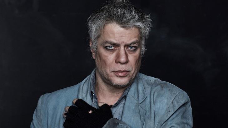 Fábio Assunção olhando fixamente para a câmera de luva e casaco sujo