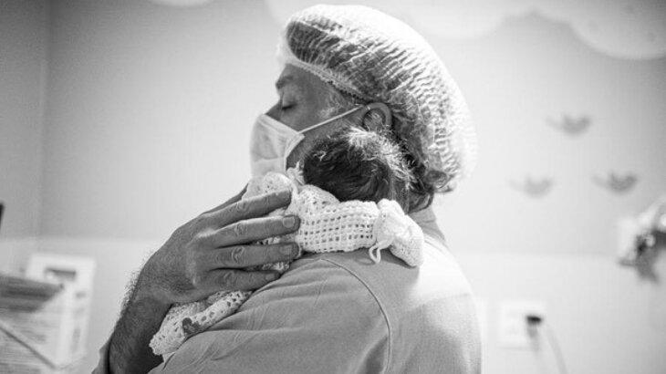 Fábio Assunção na maternidade, com olhos fechados e Alana nos braços