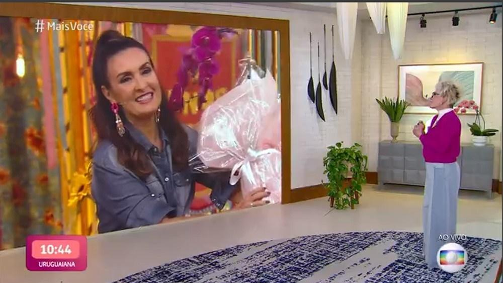 Fátima Bernardes segura flores enquanto conversa com Ana Maria Braga