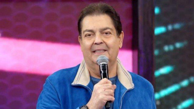 Faustão com microfone na mão e jaqueta azul