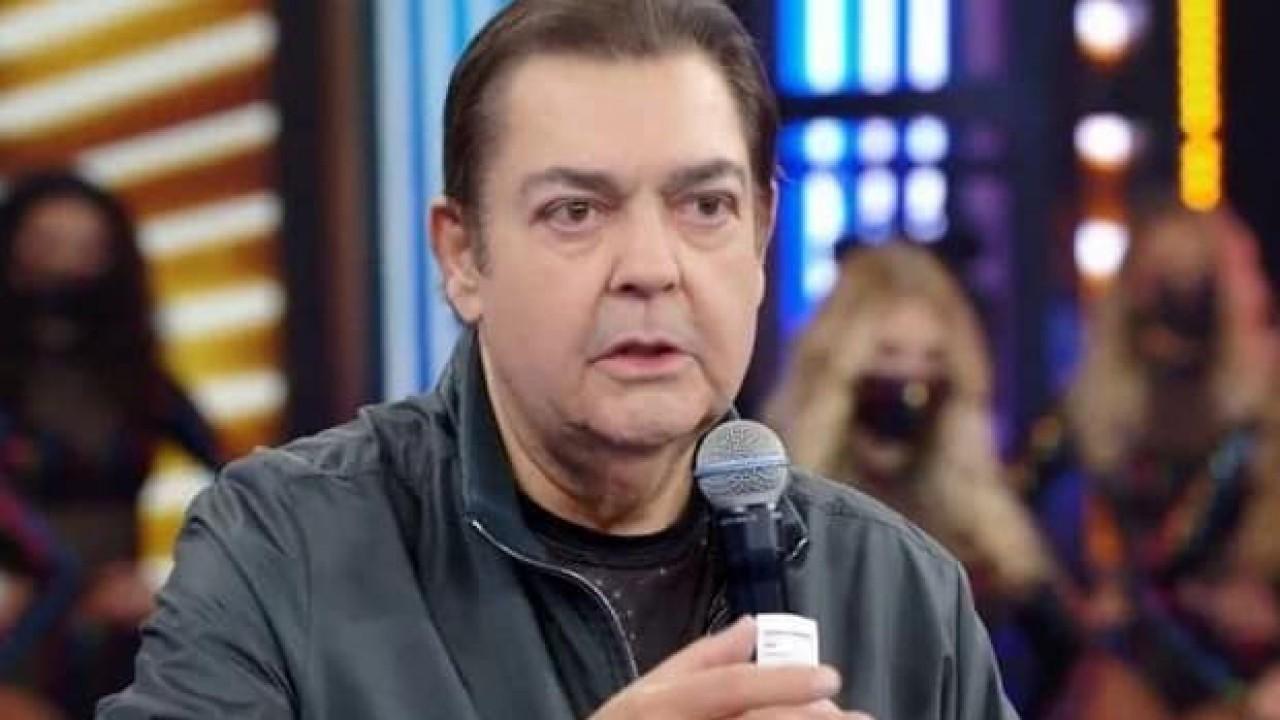 Faustão com microfone no palco do Domingão