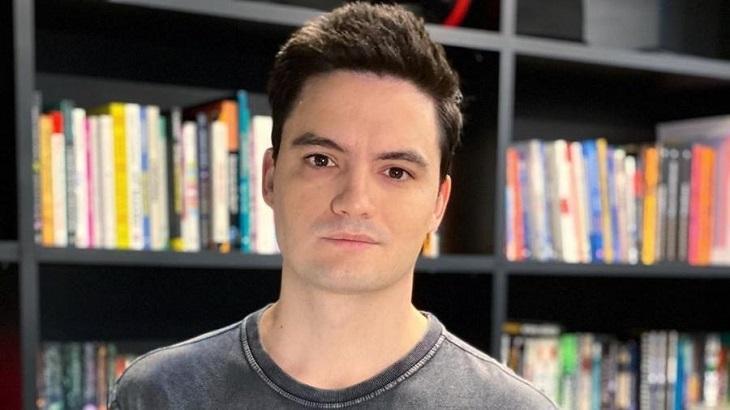 Felipe Neto sério com livros ao fundo