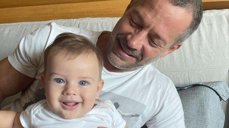 Ryan sorridente no colo de Malvino Salvador, que olha para herdeiro