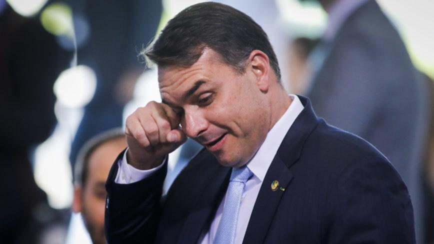 Flávio Bolsonaro com a mão nos olhos